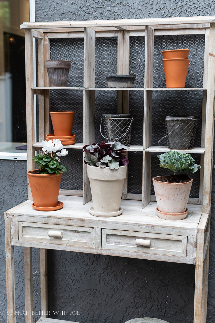 Pots and plants on a vintage looking potting bench.