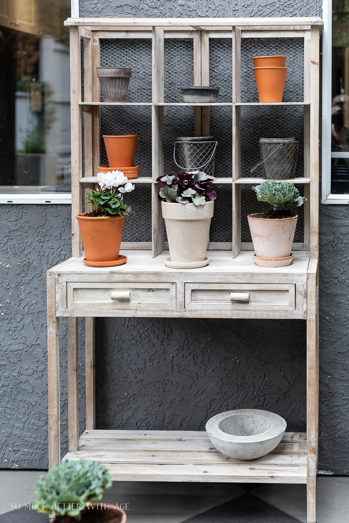 Potting bench outside with plants and pots.