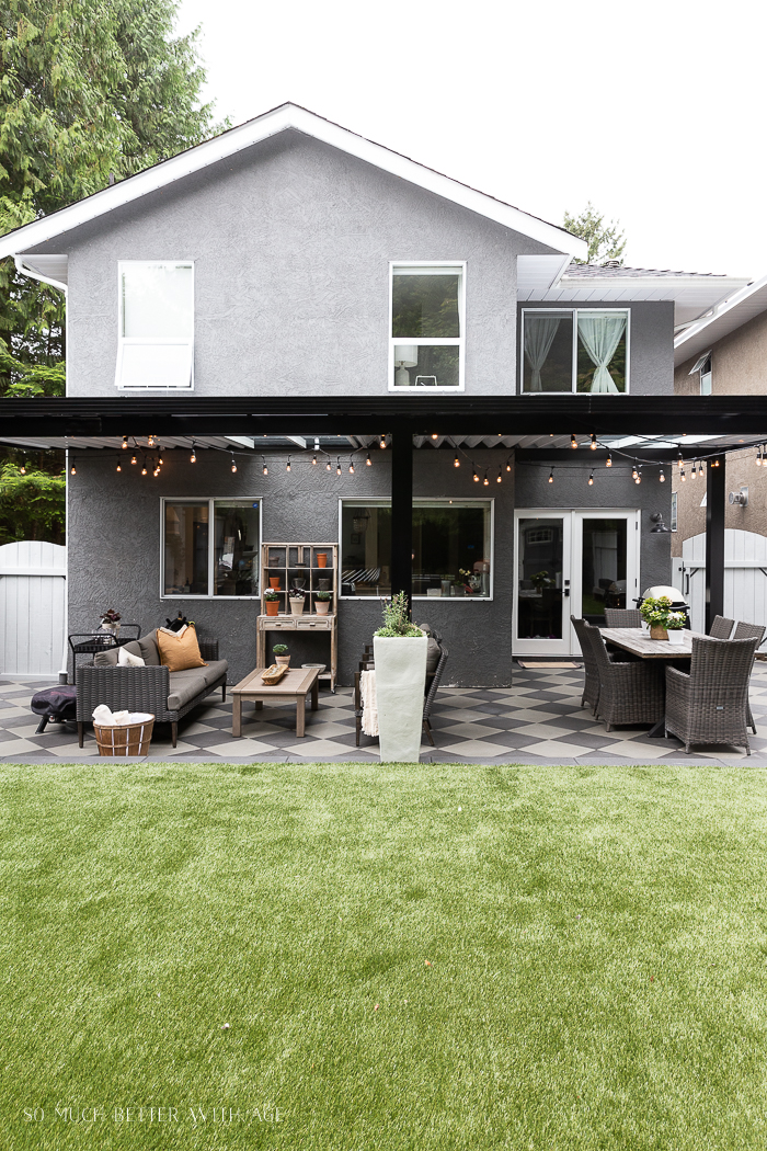 Black aluminum awning with artificial turf in backyard.
