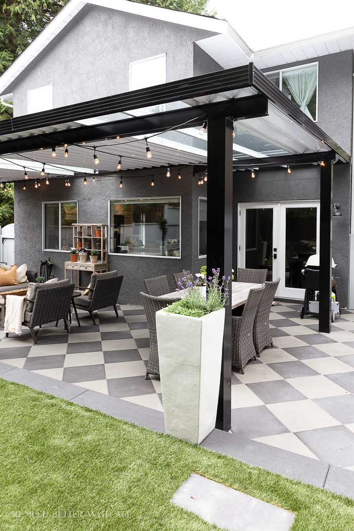 Black aluminum awning with white ceiling and checkerboard pavers.
