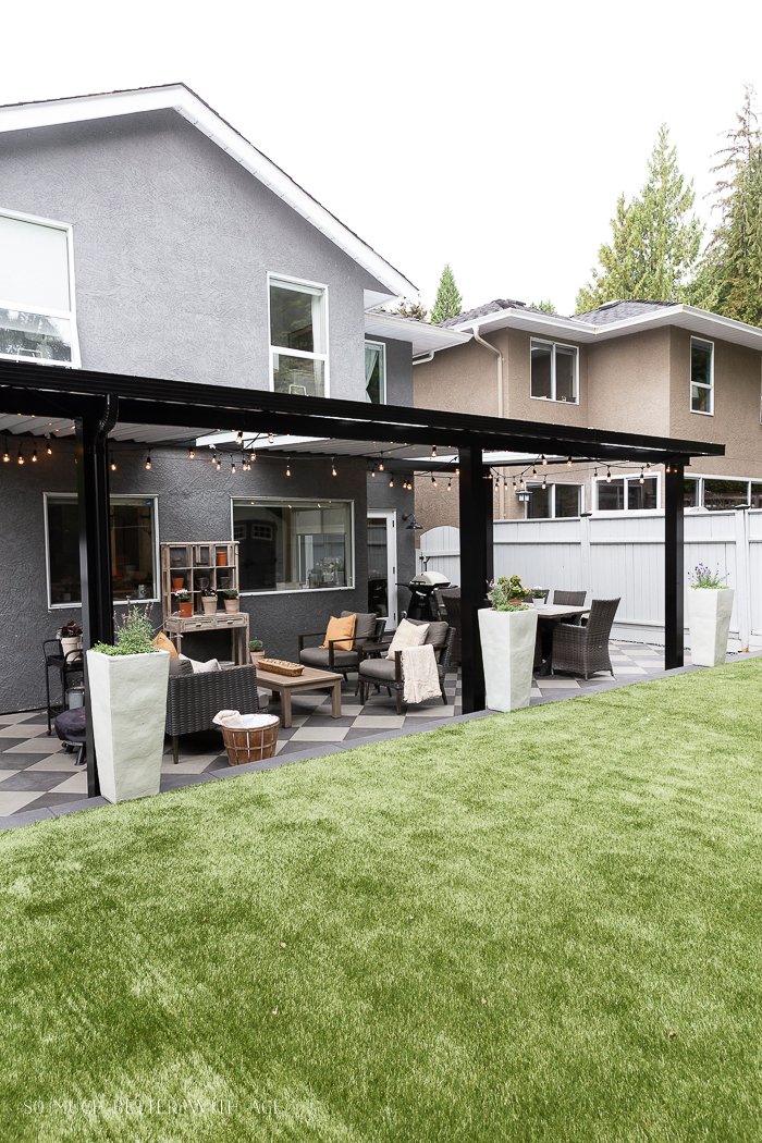 Artificial turf with black aluminum awning in backyard of grey house.