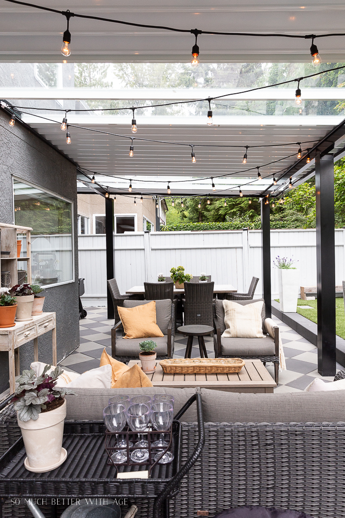 String lights in aluminum awning in backyard area.