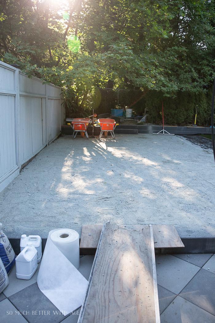 Sand tampered down on ground with orange wheelbarrows.