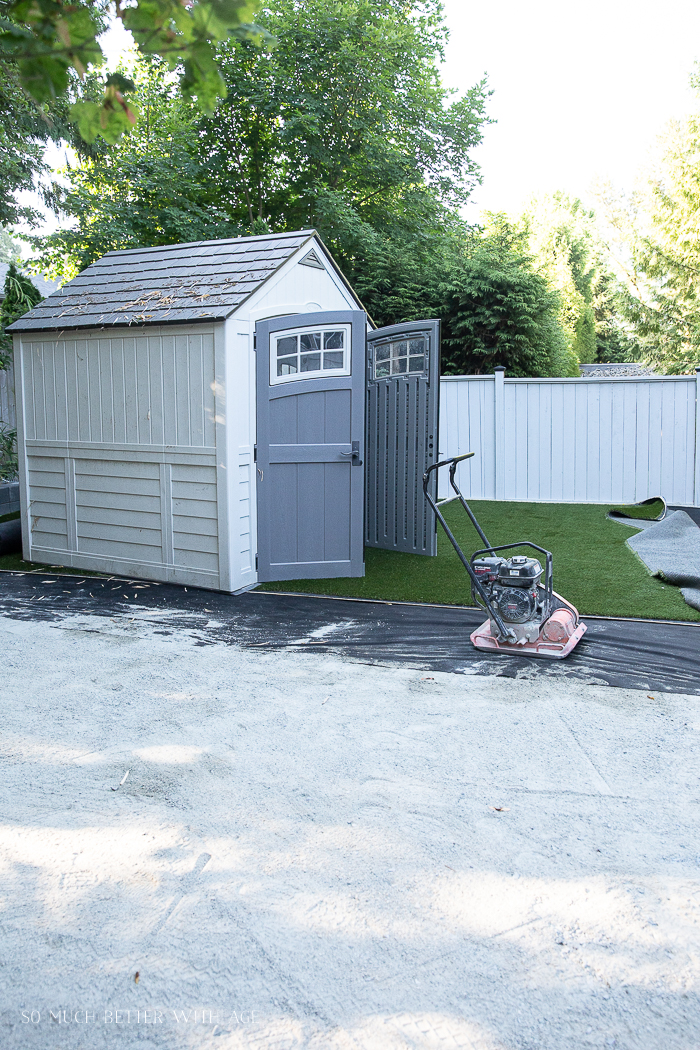 Shed sitting on artificial turf while it's getting installed.