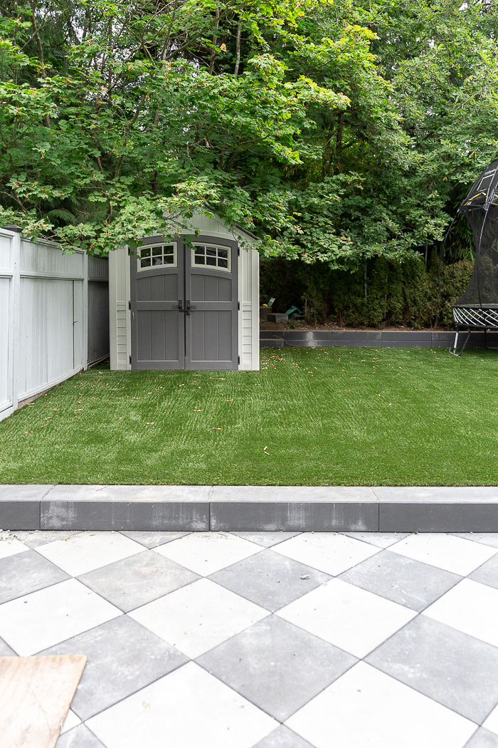 Artificial turf in backyard with checkerboard pavers.