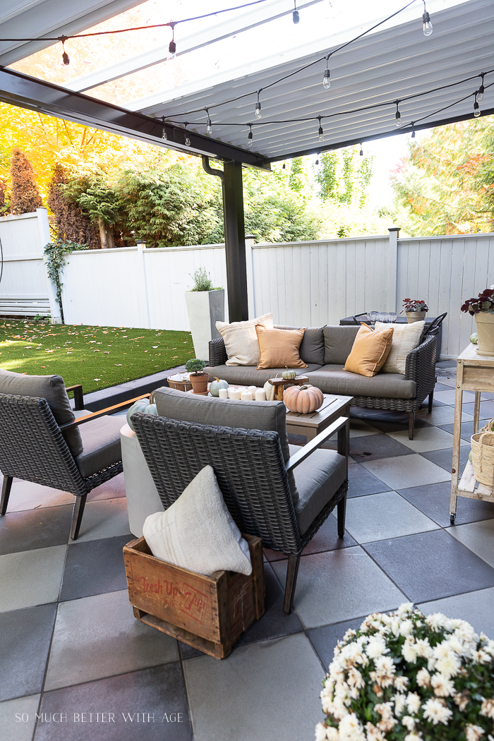 Outdoor fall patio with checkerboard pavers and pumpkins.