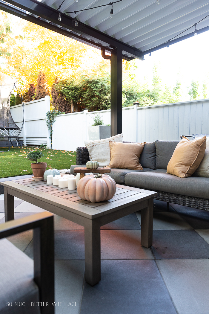 Pumpkins and candles on outdoor coffee table.
