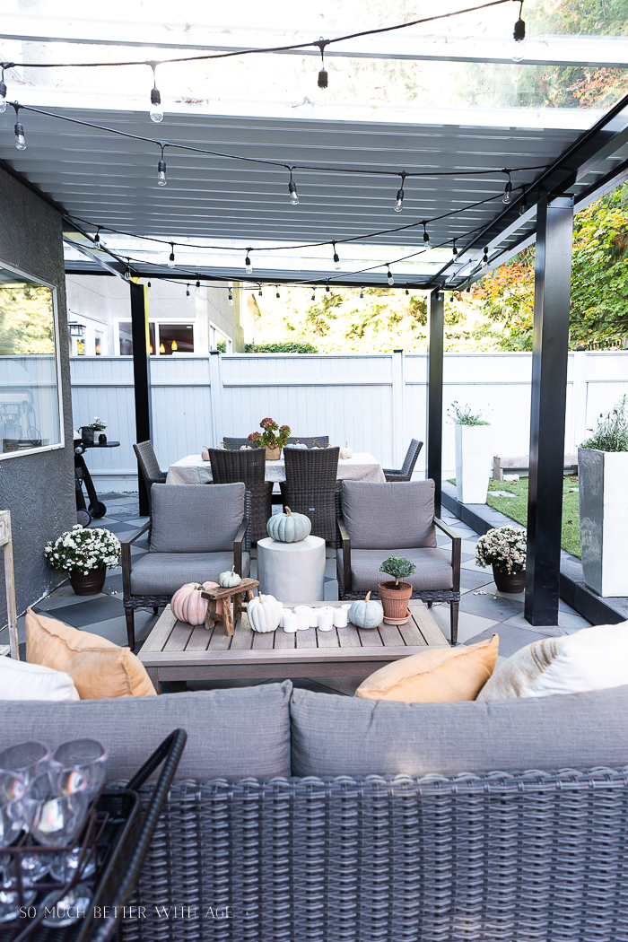 Outdoor covered patio decorated for fall with pumpkins and mums.