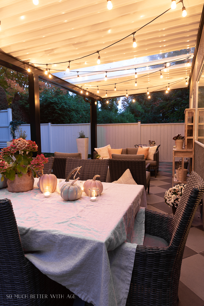 String lights on aluminum covered patio with a table decorated for fall.
