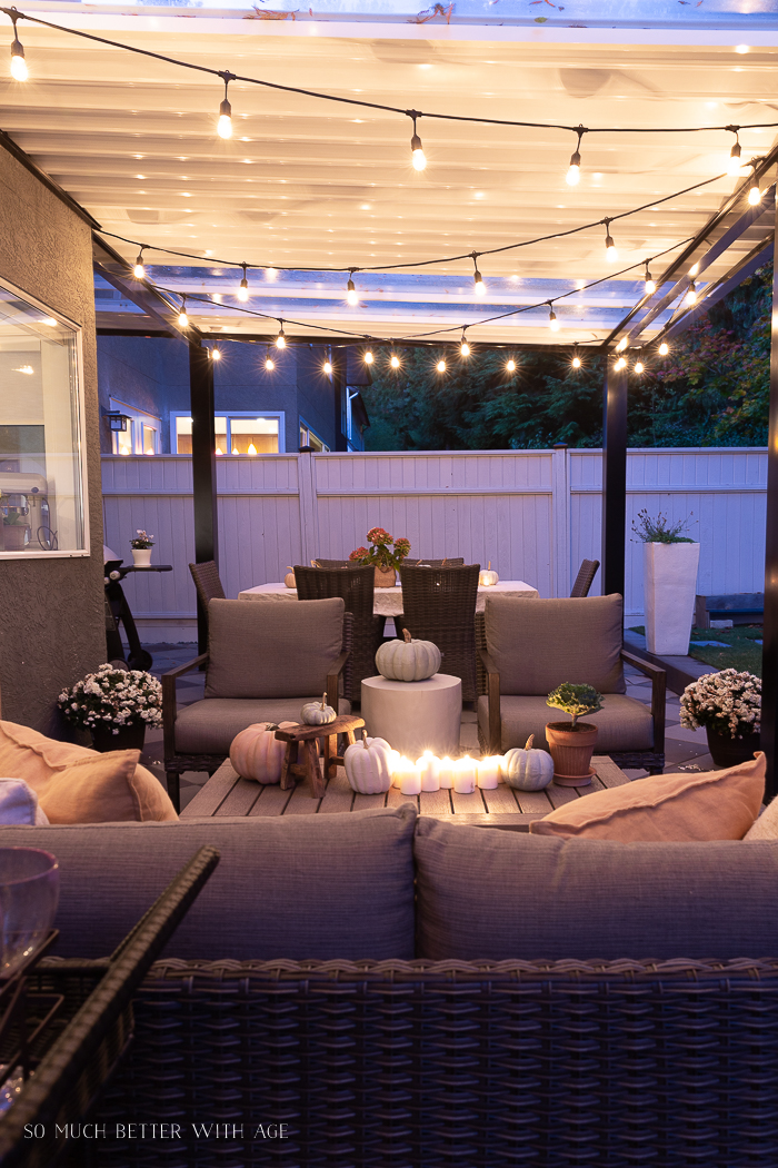 String lights on covered patio decorated for fall.
