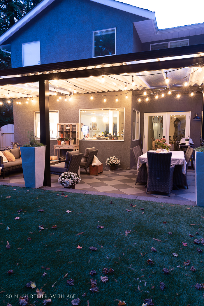 Outdoor patio with string lights at night decorated in fall.