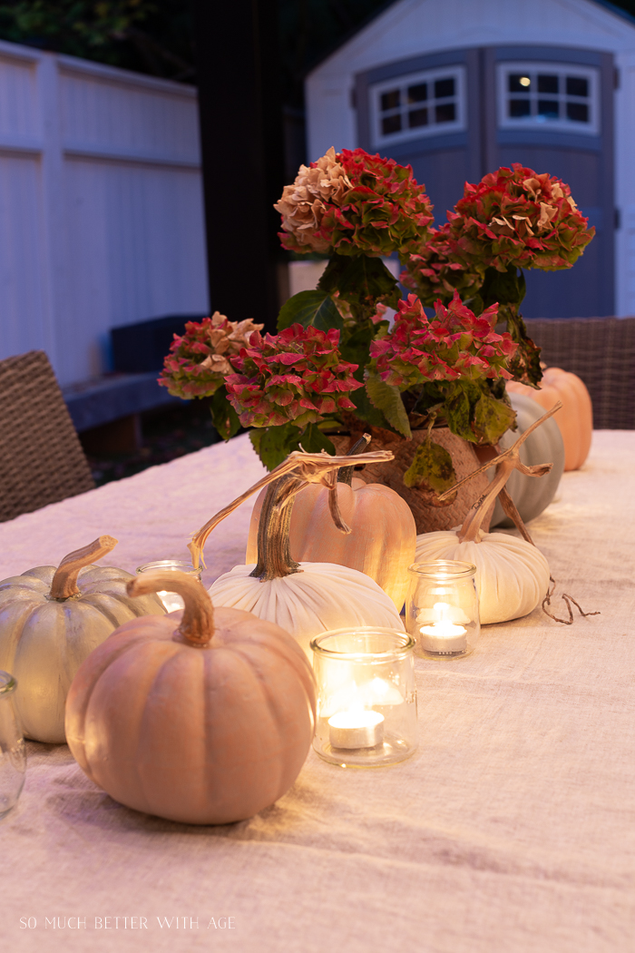 Fall flowers and pumpkins on candlelit table.